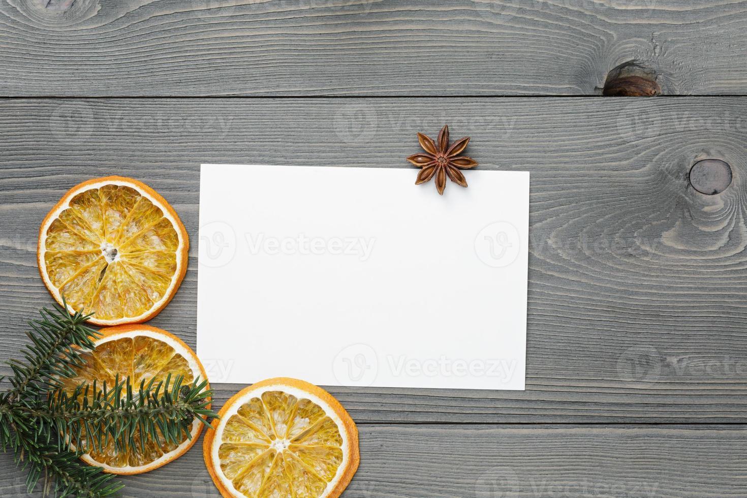 Fichtenzweig mit getrockneten Orangenscheiben und Grußkarte foto