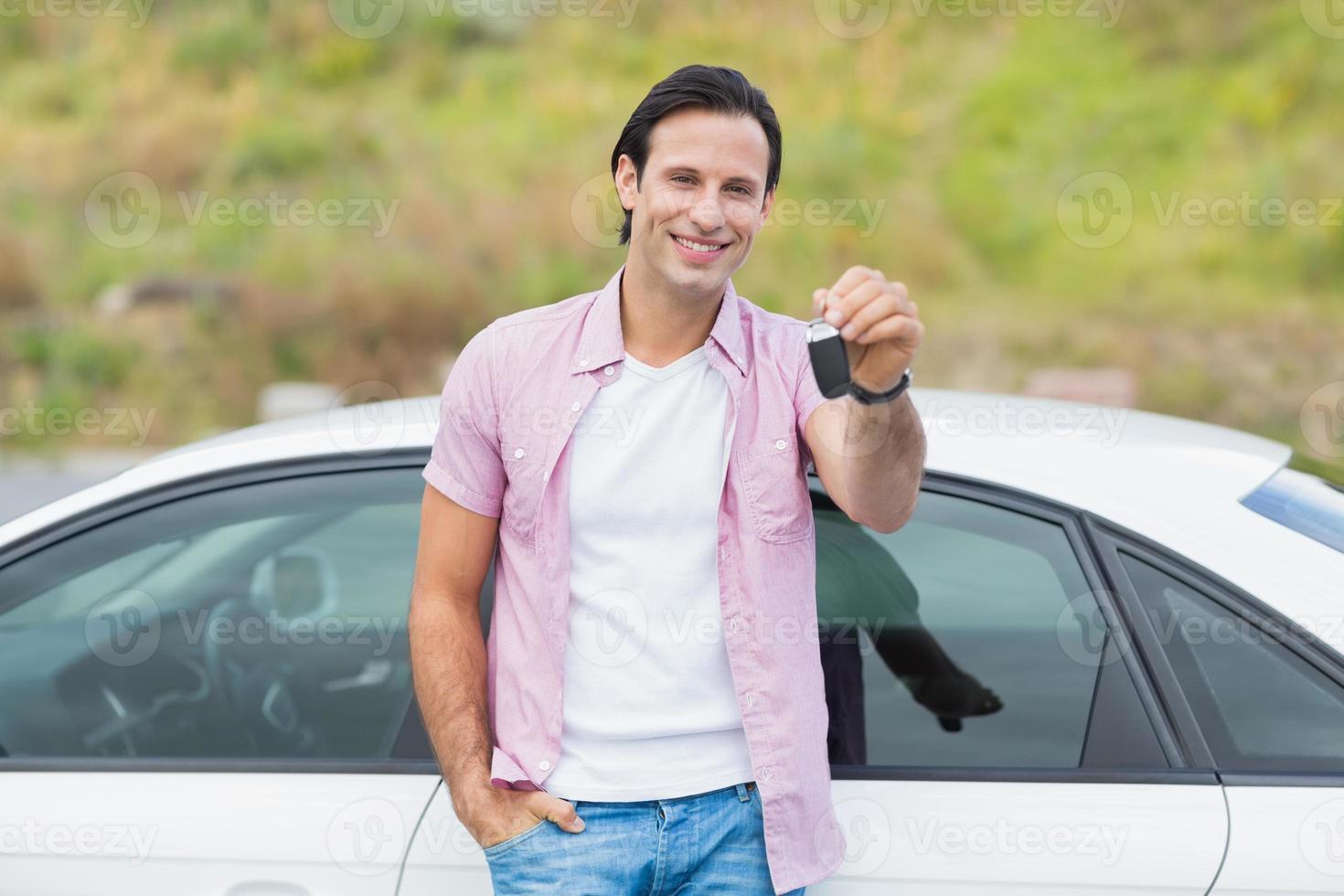 Mann an die Tür gelehnt und Schlüssel halten foto