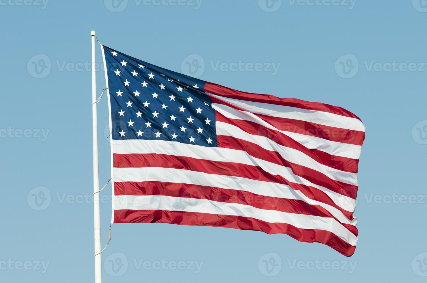 amerikanische Flagge, die im blauen Himmel weht foto