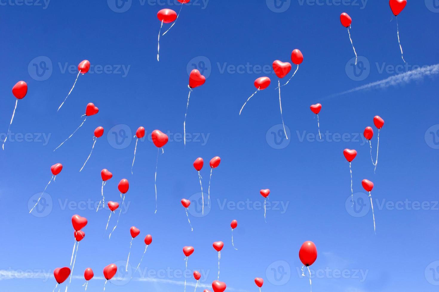 rote Herzballons in einem blauen Himmel foto