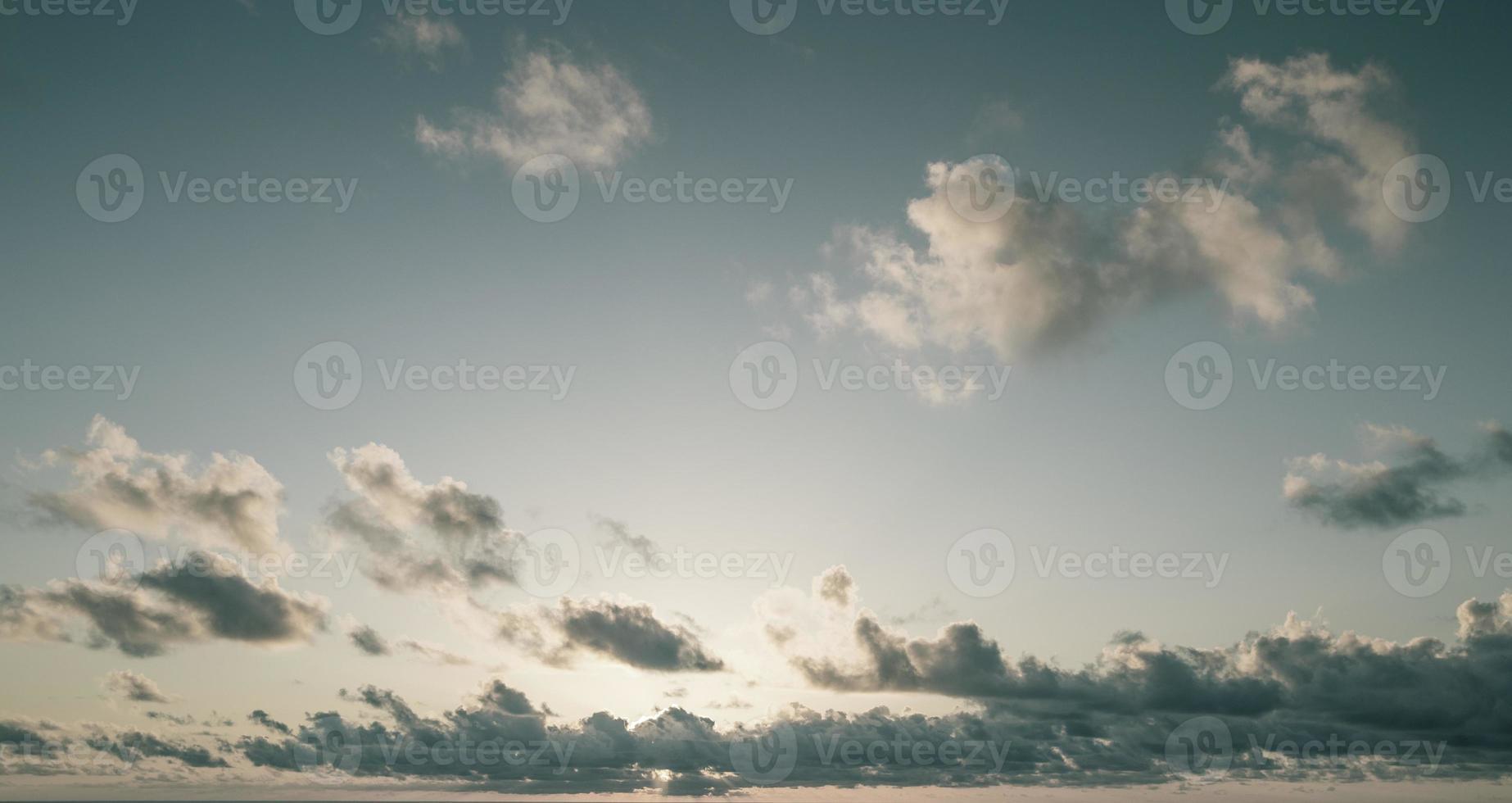blauer Himmel mit flauschigen Wolken bei Sonnenaufgang foto