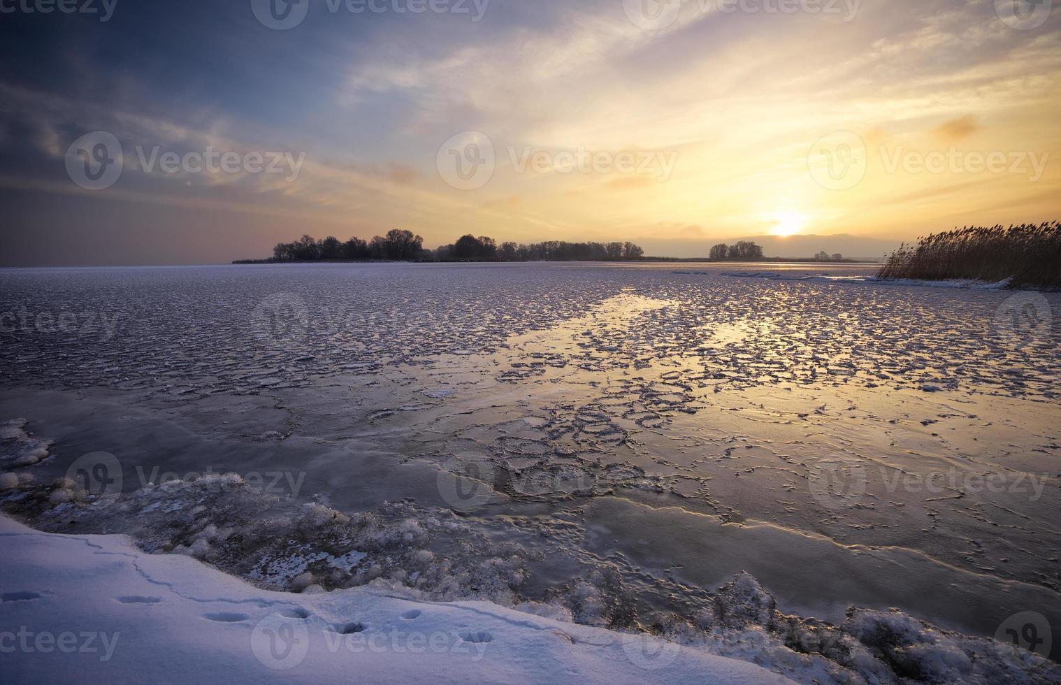 Winterlandschaft mit See und Sonnenuntergang feurigen Himmel. foto