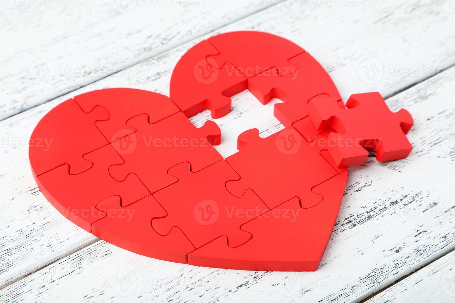 rotes Puzzleherz auf weißem hölzernem Hintergrund foto