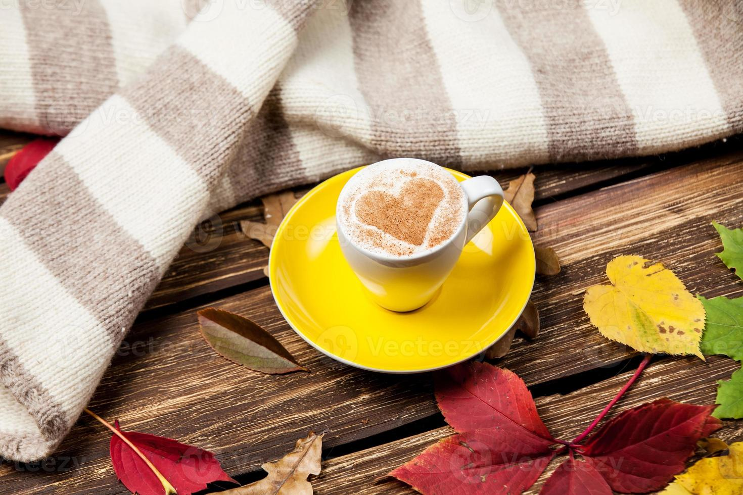 Herbstblätter, Schal und Kaffeetasse auf Holztisch. foto