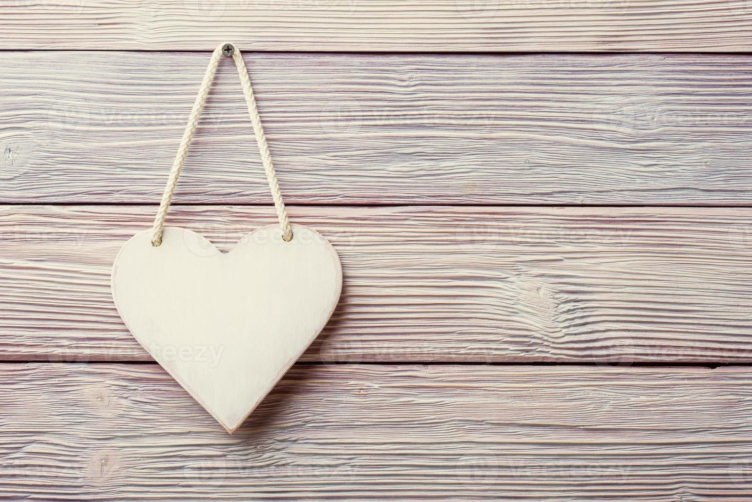 weißes Herz hängt über hellem hölzernen Weinlesehintergrund foto