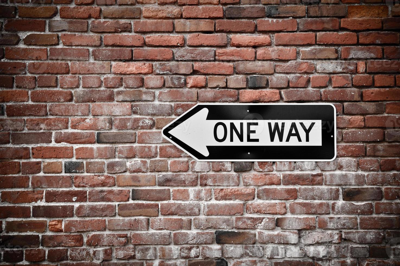 Einwegzeichen mit Grunge Backsteinmauer Hintergrund foto