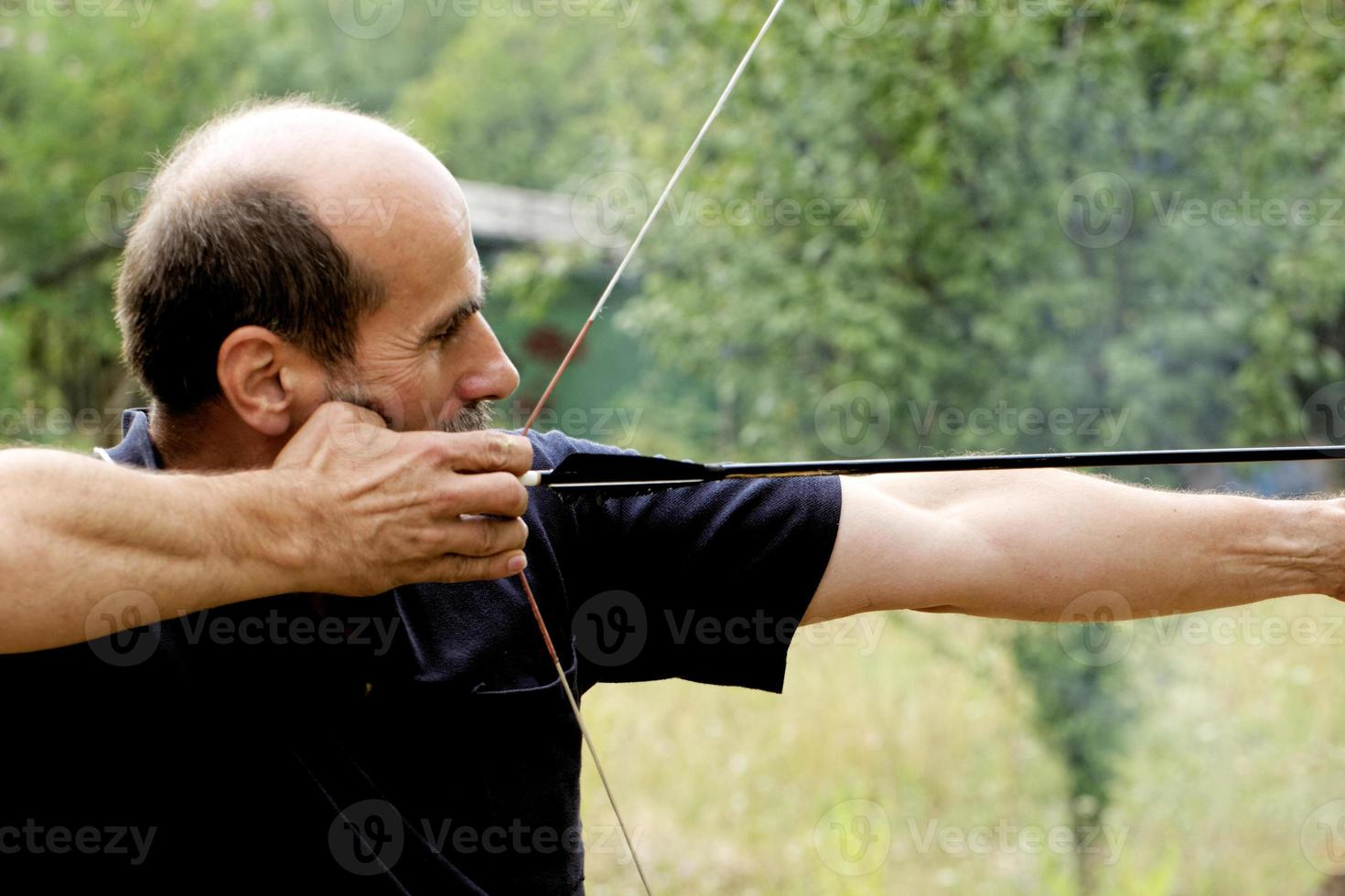 Mann schießt mit Bogen foto