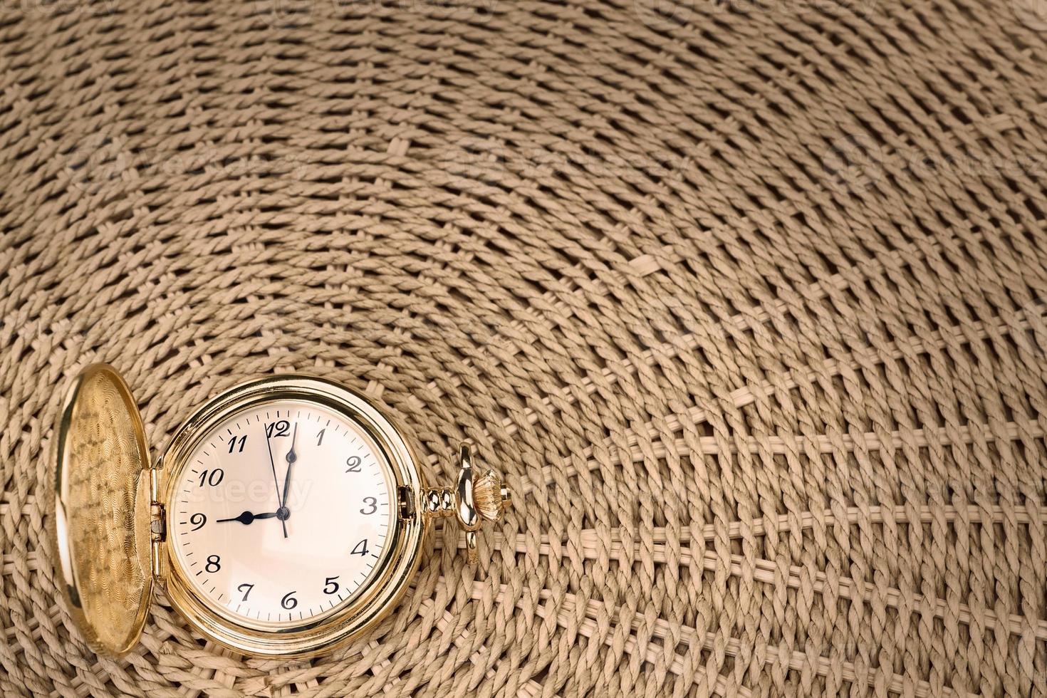 antike Taschenuhr auf einem strukturierten gewebten Strohhalm. Nahansicht. foto