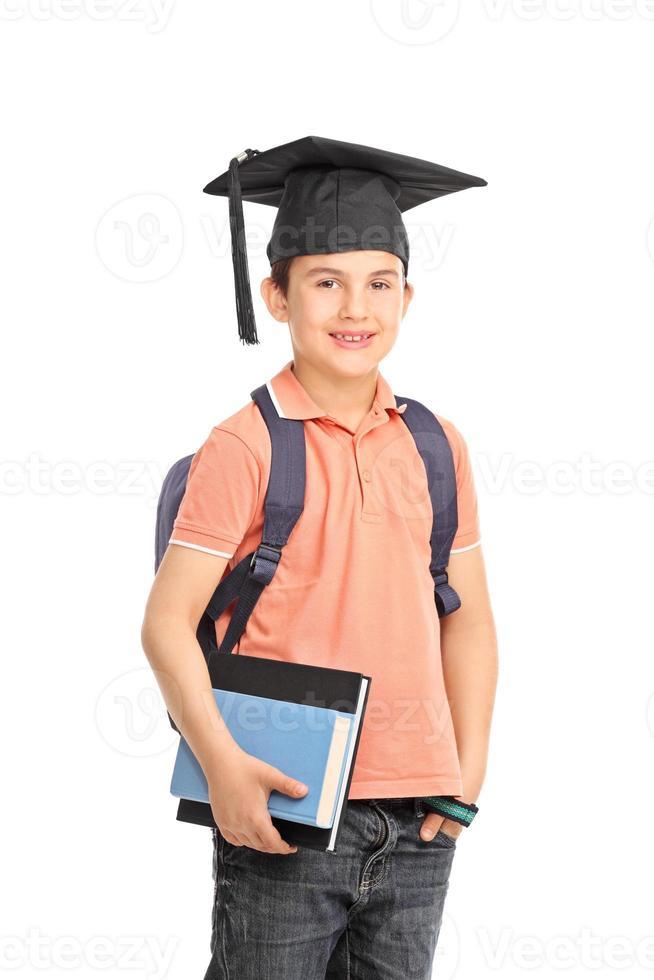 Schüler mit einem Abschlusshut, der Bücher hält foto