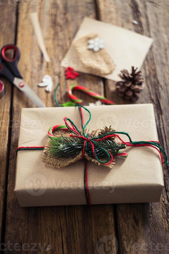 Weihnachtsgeschenke auf einem hölzernen Hintergrund mit Zuckerstange foto