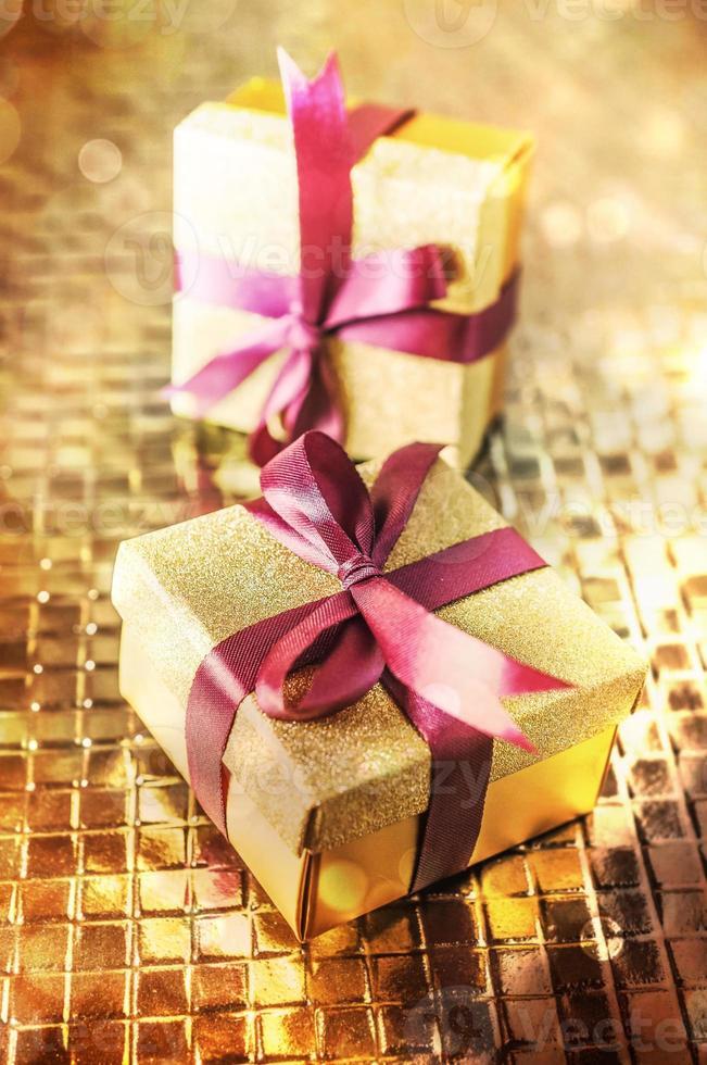 Weihnachtsgeschenke mit lila Band auf Goldhintergrund foto