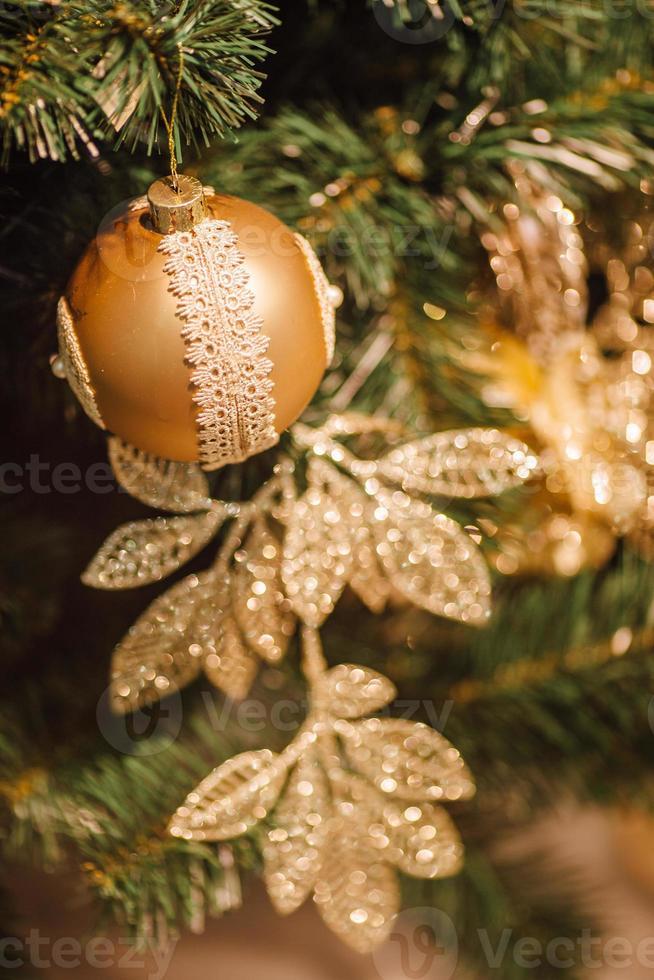 goldener Weihnachtshintergrund von defokussierten Lichtern mit geschmücktem Baum foto