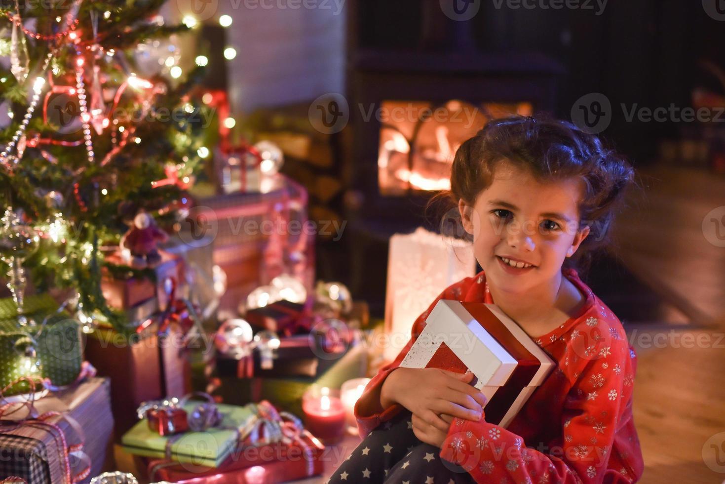 Weihnachtszeit, kleines Mädchen öffnet ein Geschenk in der Nähe von Baum beleuchtet foto