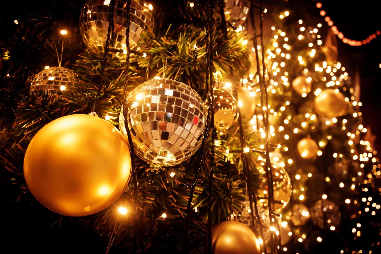 Weihnachtsbaum mit Goldkugel und Bokeh beleuchtet Hintergrund foto