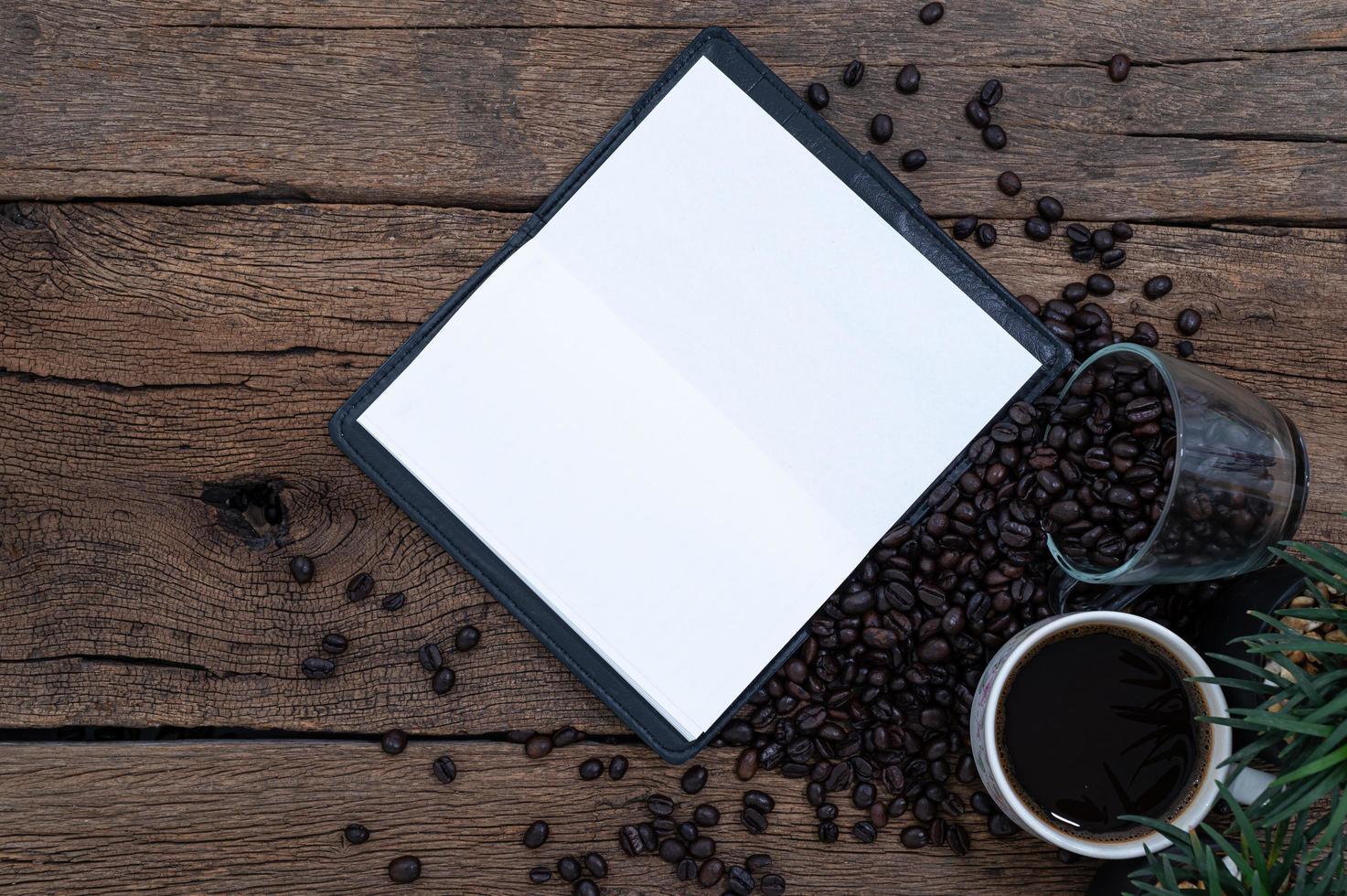 Kaffeetassen, Kaffeebohnen und ein Rekordbuch foto