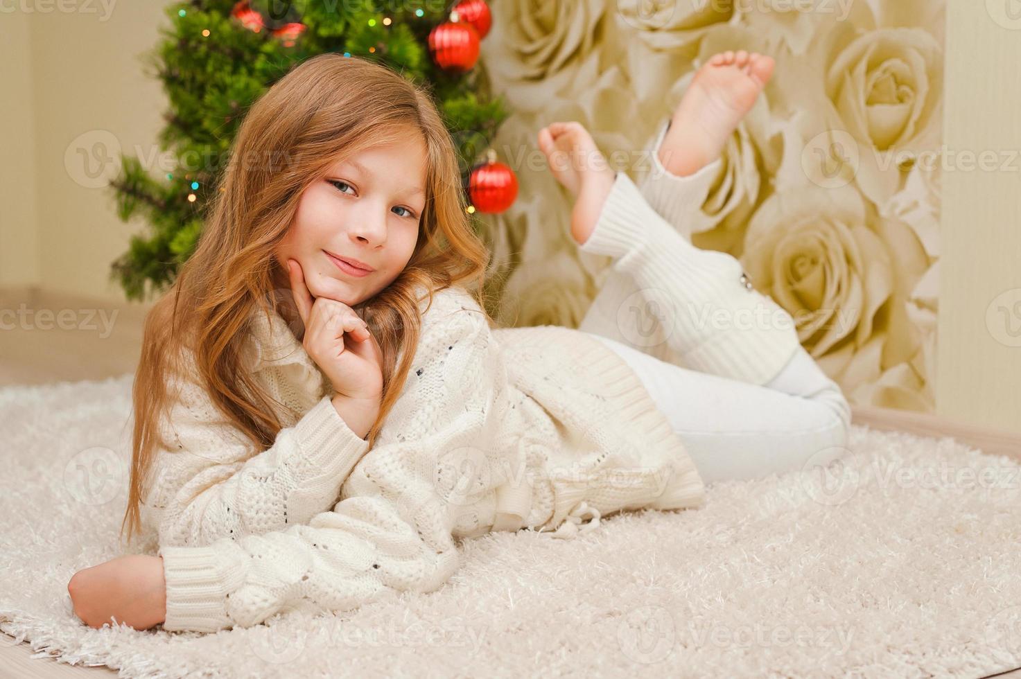Mädchen, das auf dem Teppich nahe dem Weihnachtsbaum liegt. foto