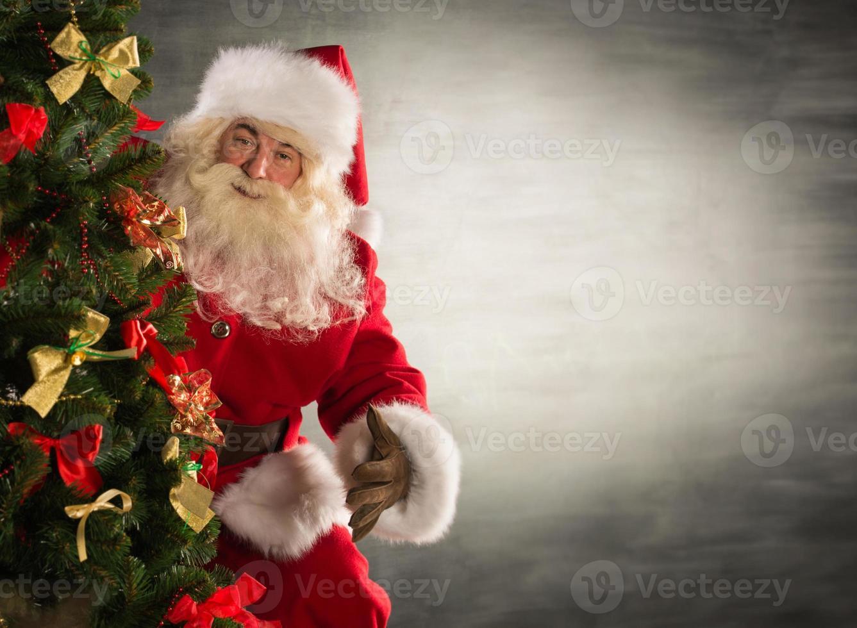 Weihnachtsmann steht in der Nähe von Weihnachtsbaum foto