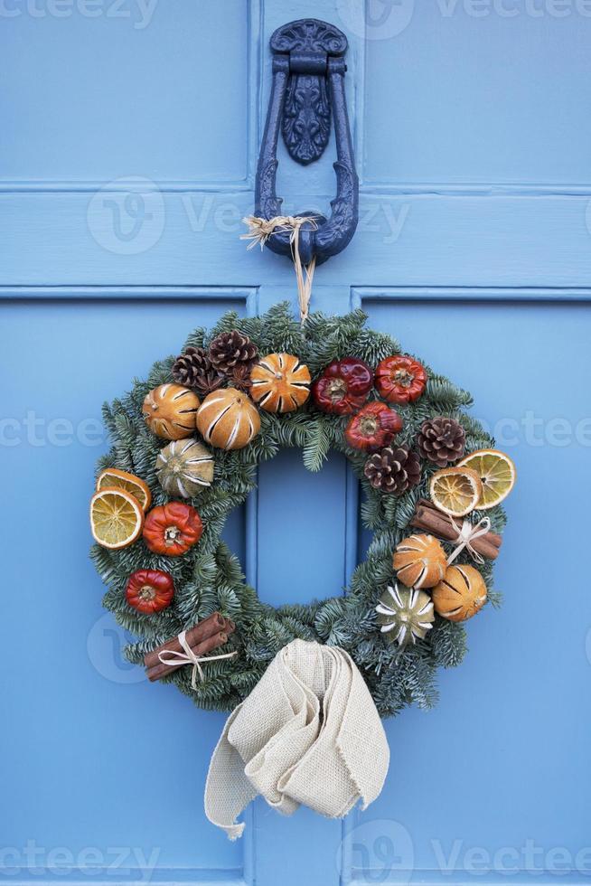 hausgemachter Weihnachtskranz, der an der blauen Tür hängt foto