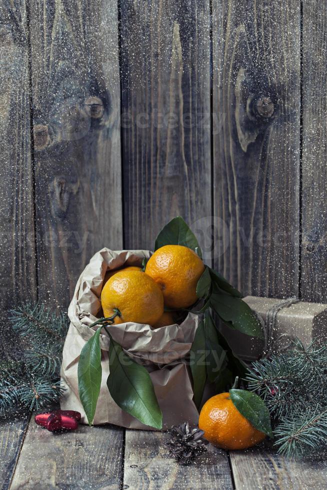 Weihnachtsdekoration und Mandarinen auf hölzernem Hintergrund foto