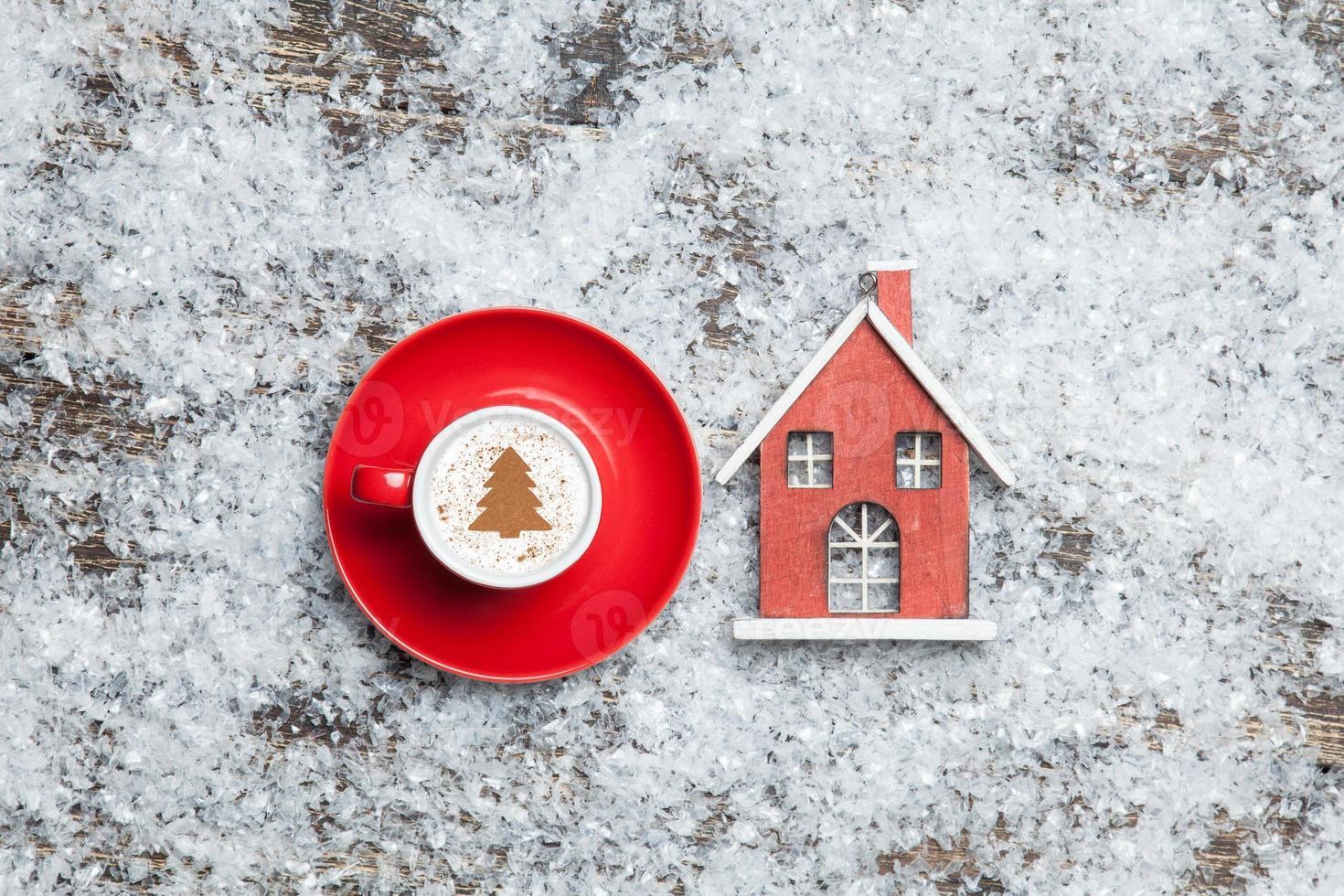 Cappuccino mit Weihnachtsbaumform und Spielzeughaus auf künstlichem foto