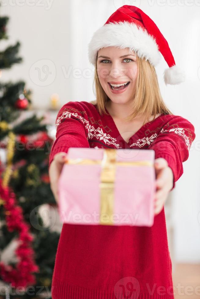 lächelnde festliche Frau, die ein rosa Geschenk anbietet foto