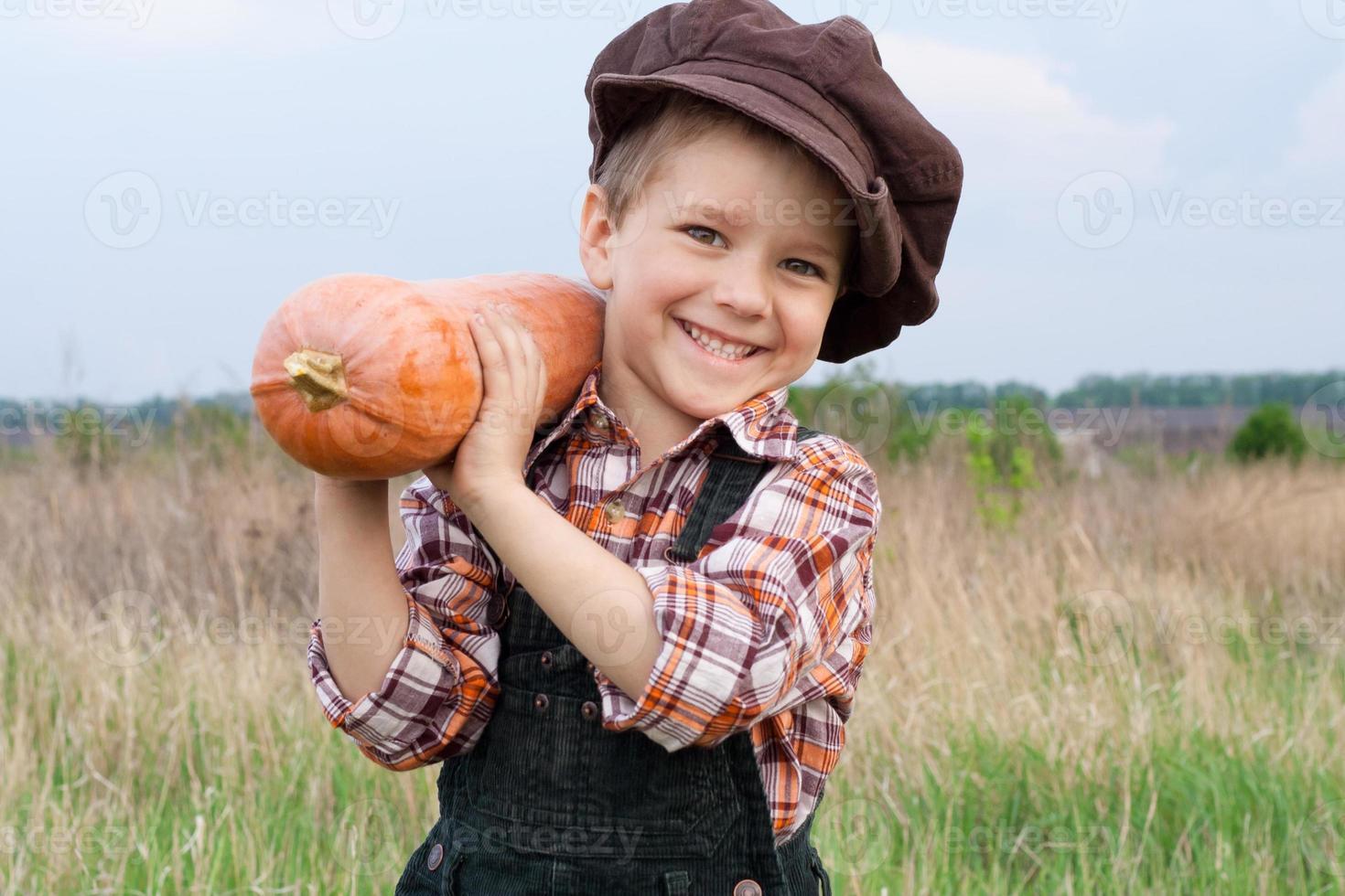 lächelnder Junge mit Kürbis auf seiner Schulter foto