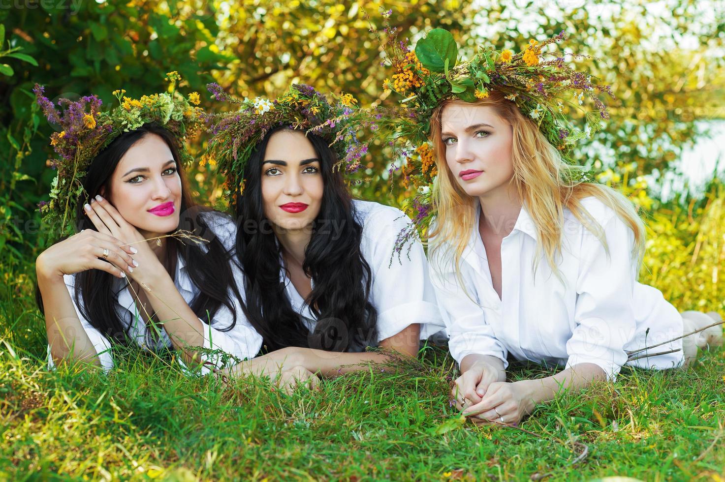 drei charmante Frau, die auf dem Gras mit Blumenkranz liegt foto