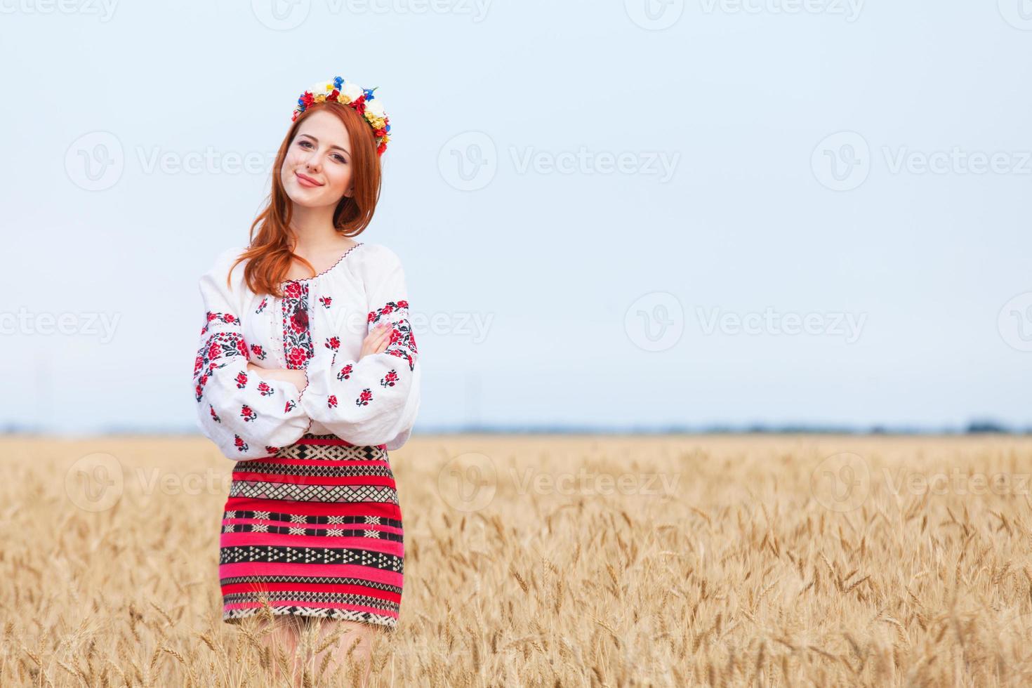 rothaariges Mädchen in der ukrainischen nationalen Kleidung auf dem Weizenfeld. foto