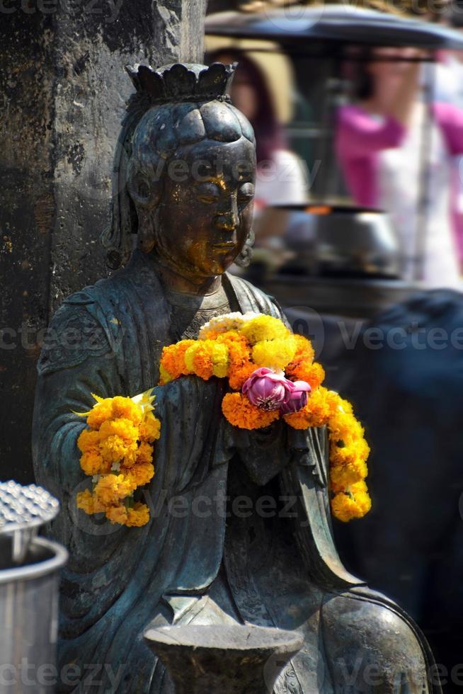 betende Buddha-Statue mit Ringelblumen foto