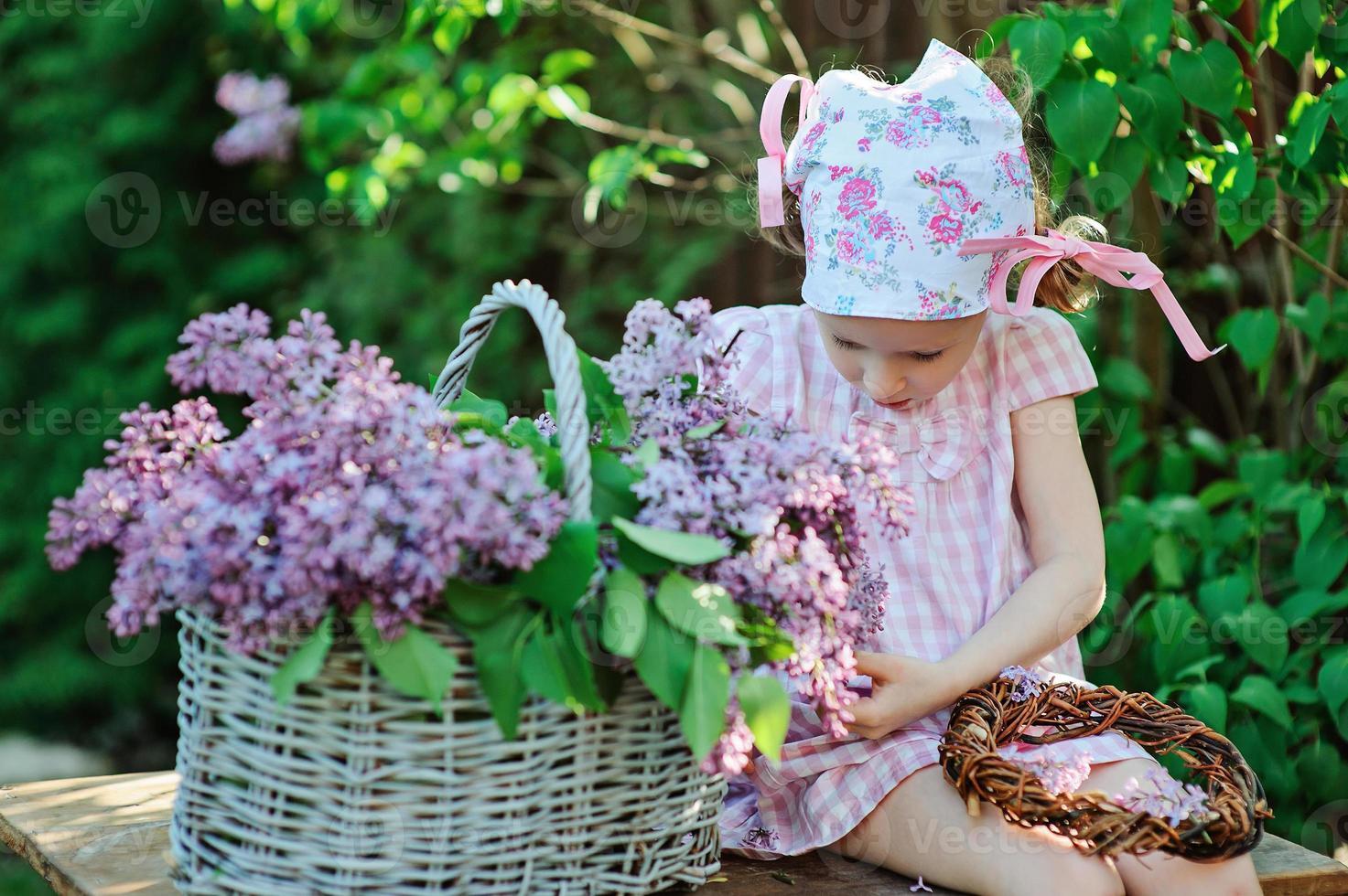 niedliches Kindermädchen, das Fliederkranz im blühenden Garten des Frühlings macht foto
