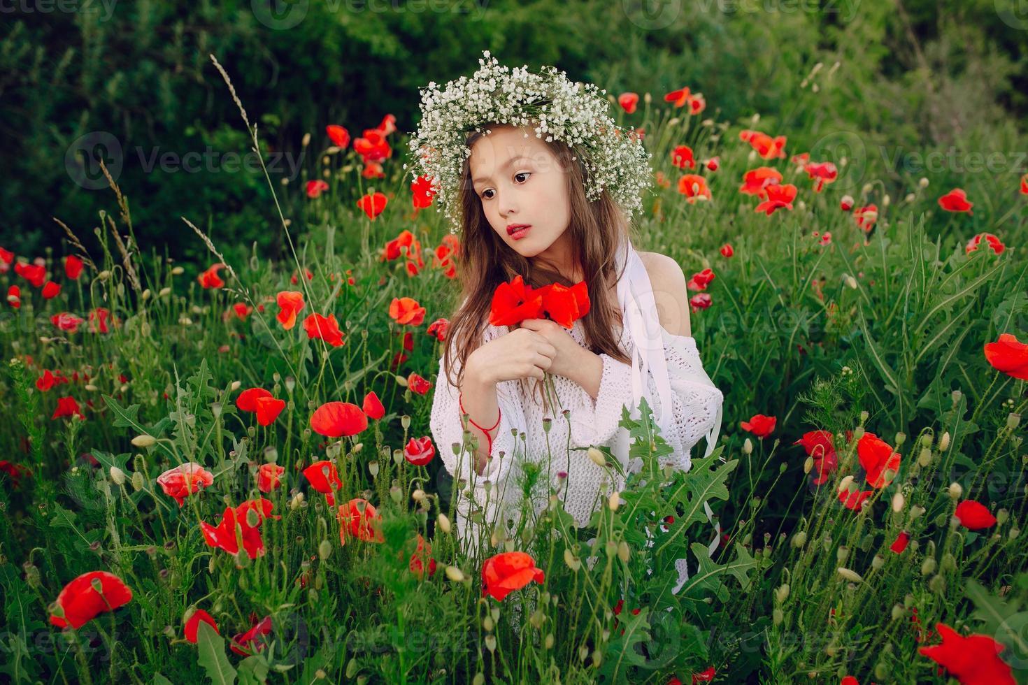 schönes kleines Mädchen, das in einem Rockkranz von Mohnblumen aufwirft foto