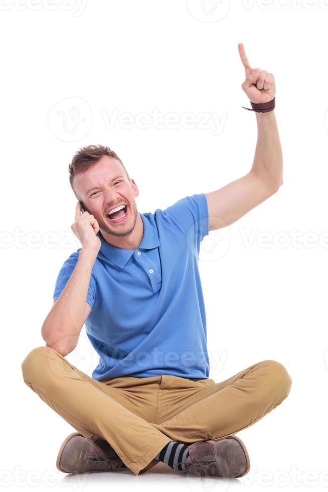 junger lässiger Mann auf seinem Telefon zeigt nach oben foto