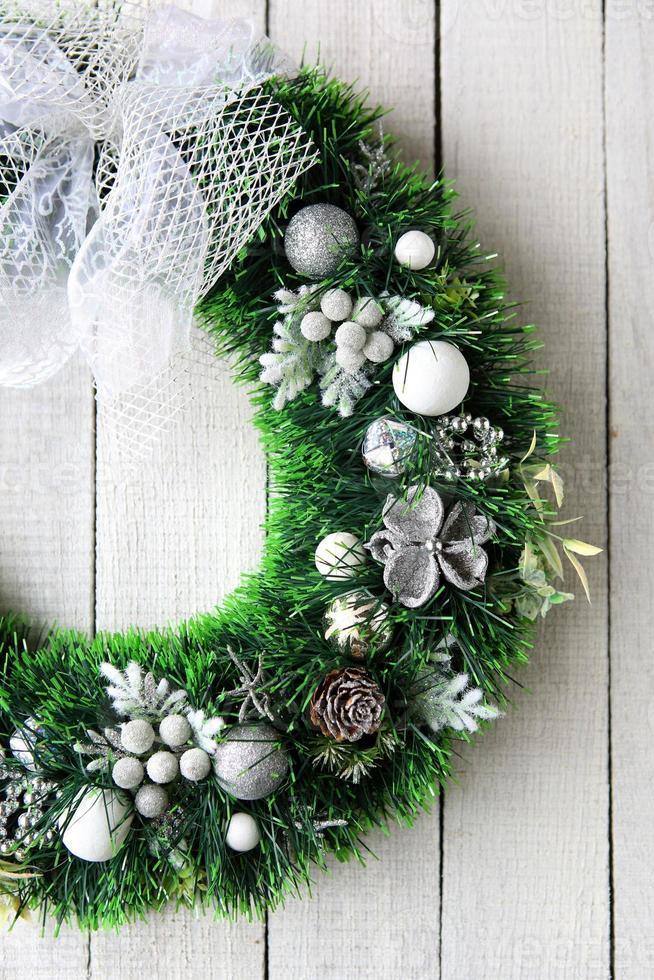 Weihnachtskranz in Silber auf weißer Tür foto