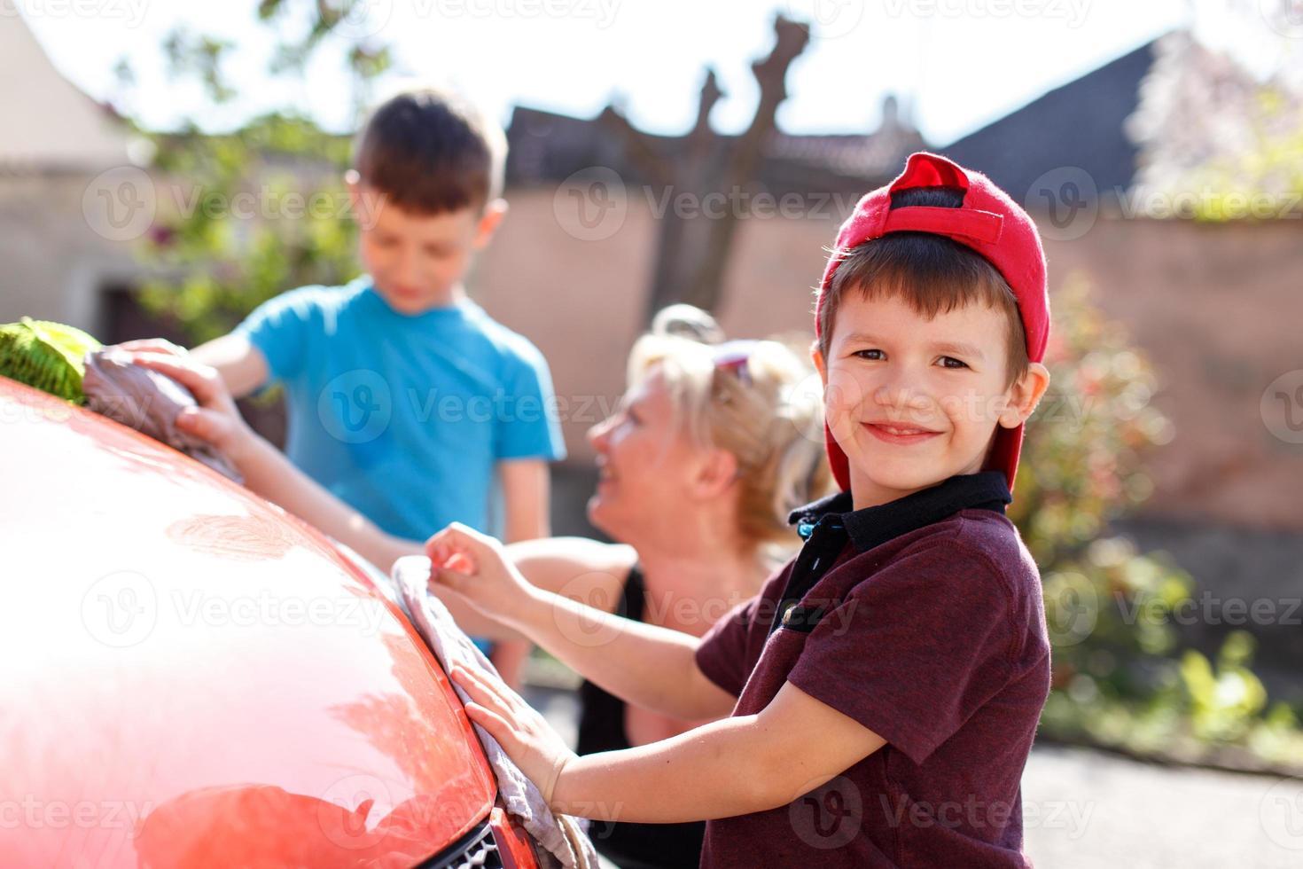 glückliches kleines Kind Autowäsche mit Familie foto