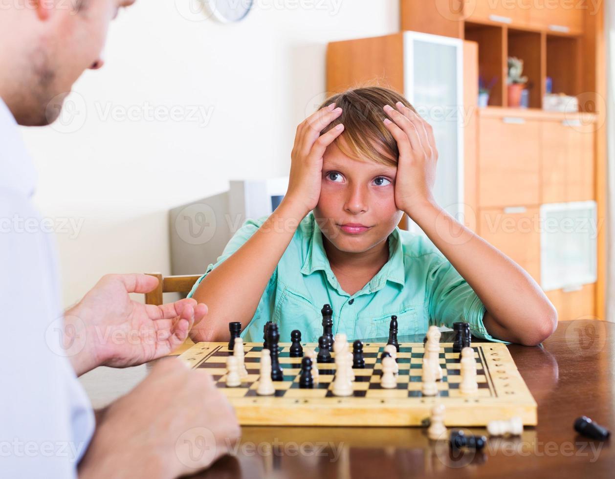 Vater und Sohn spielen Schach foto