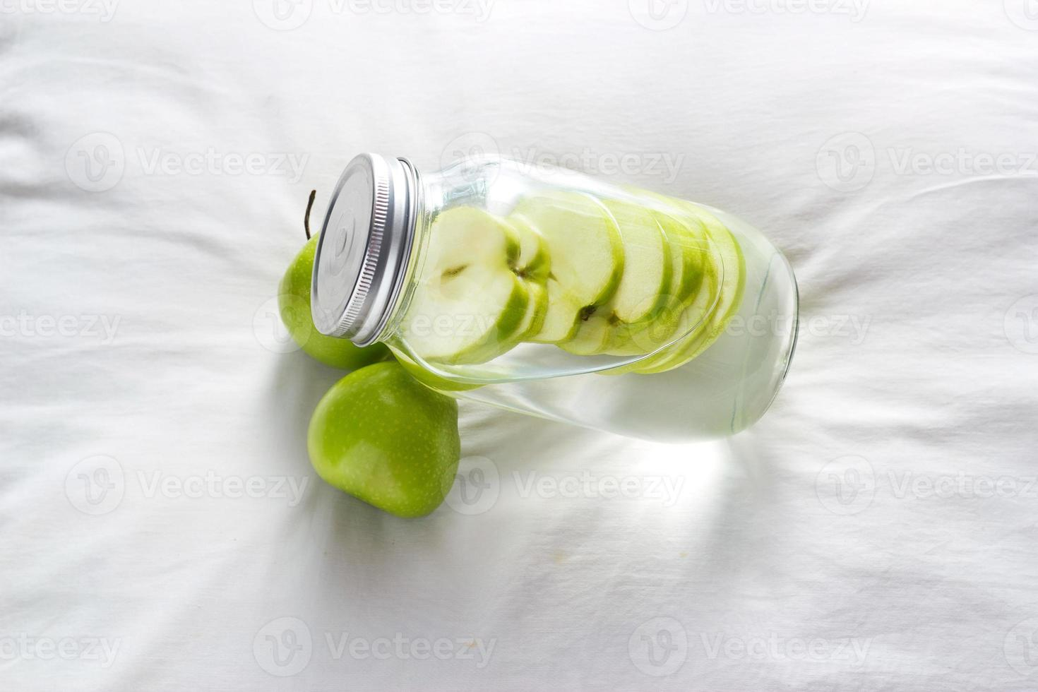Entgiftungsdiät frische grüne Äpfel in Wasser des Glases einweichen foto
