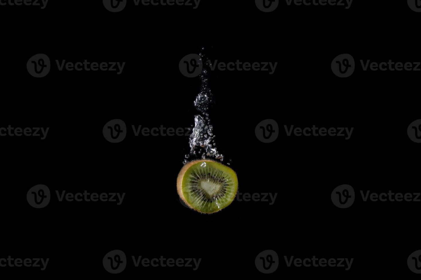 frisches Obst fiel mit Spritzer auf schwarzem Hintergrund ins Wasser foto