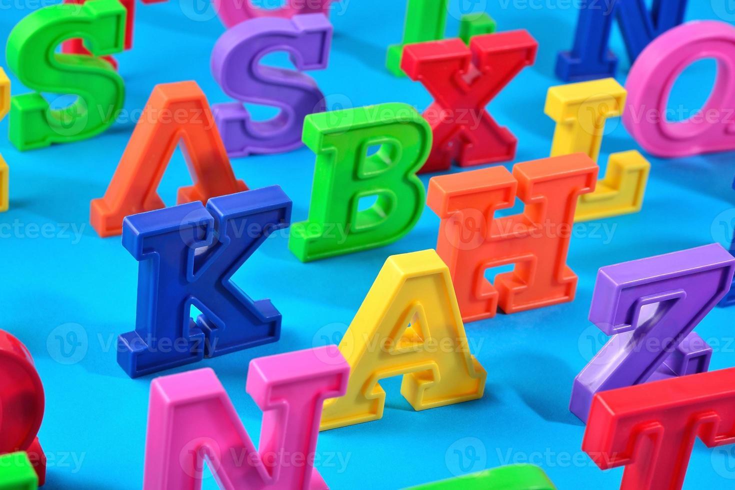 bunte Alphabetbuchstaben aus Kunststoff auf blauem Grund foto