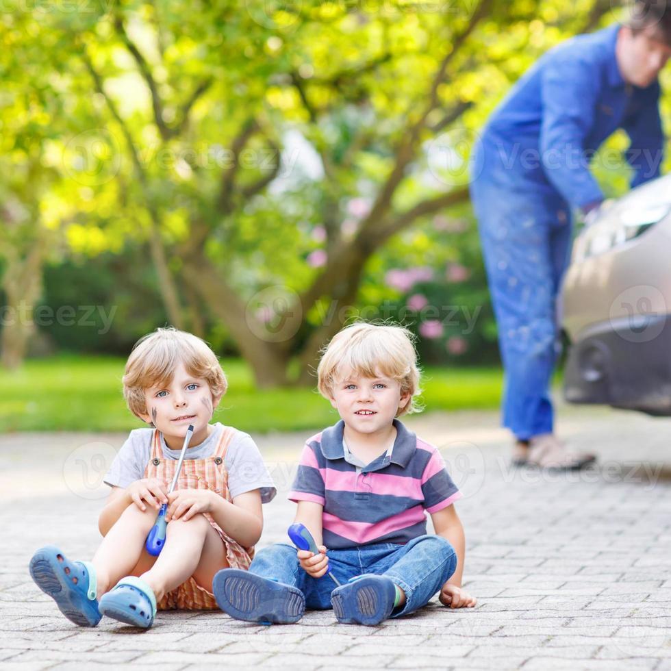 zwei kleine Geschwisterjungen und Vater reparieren Familienauto foto