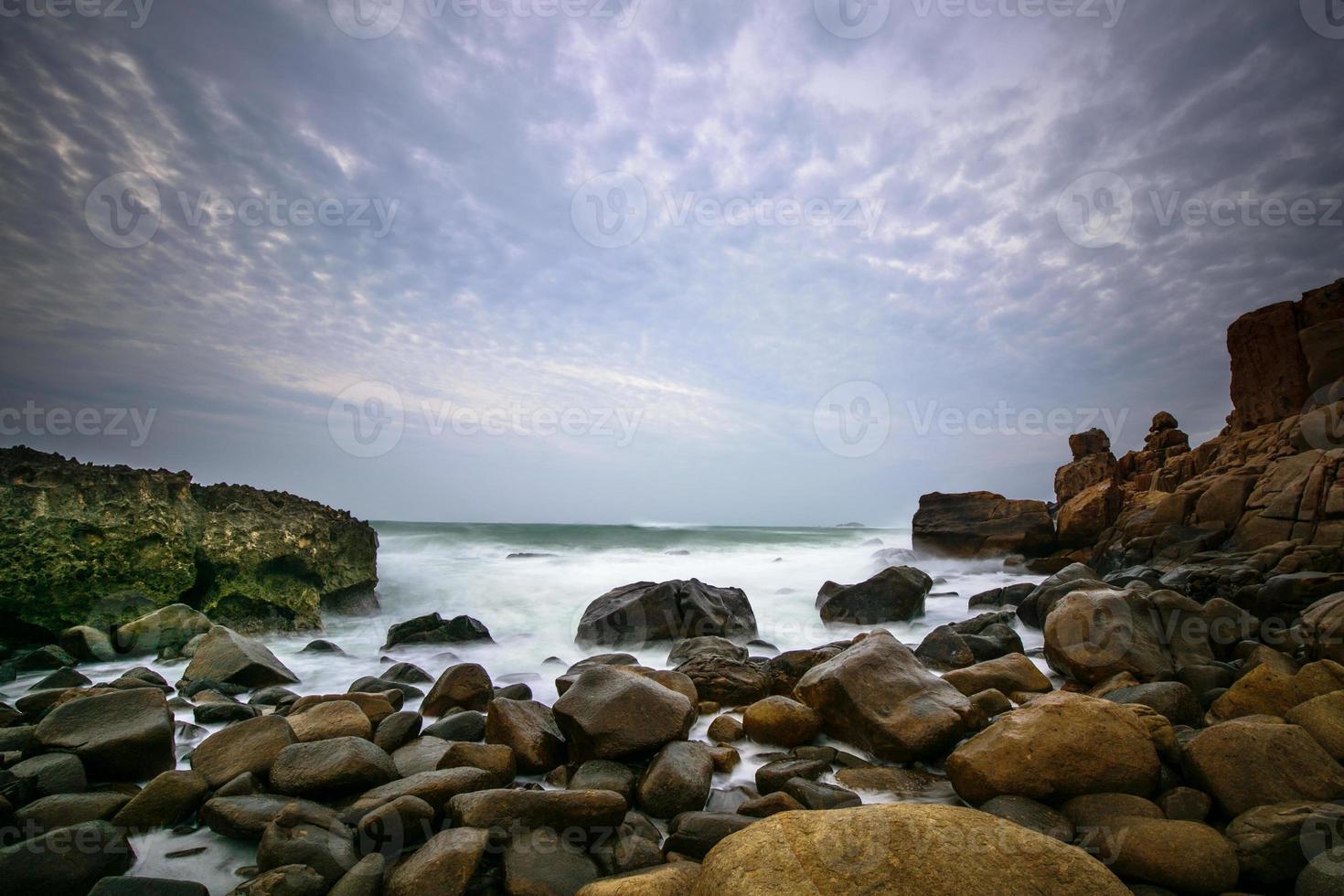 Wellen, die im Morgengrauen am felsigen Ufer krachen foto