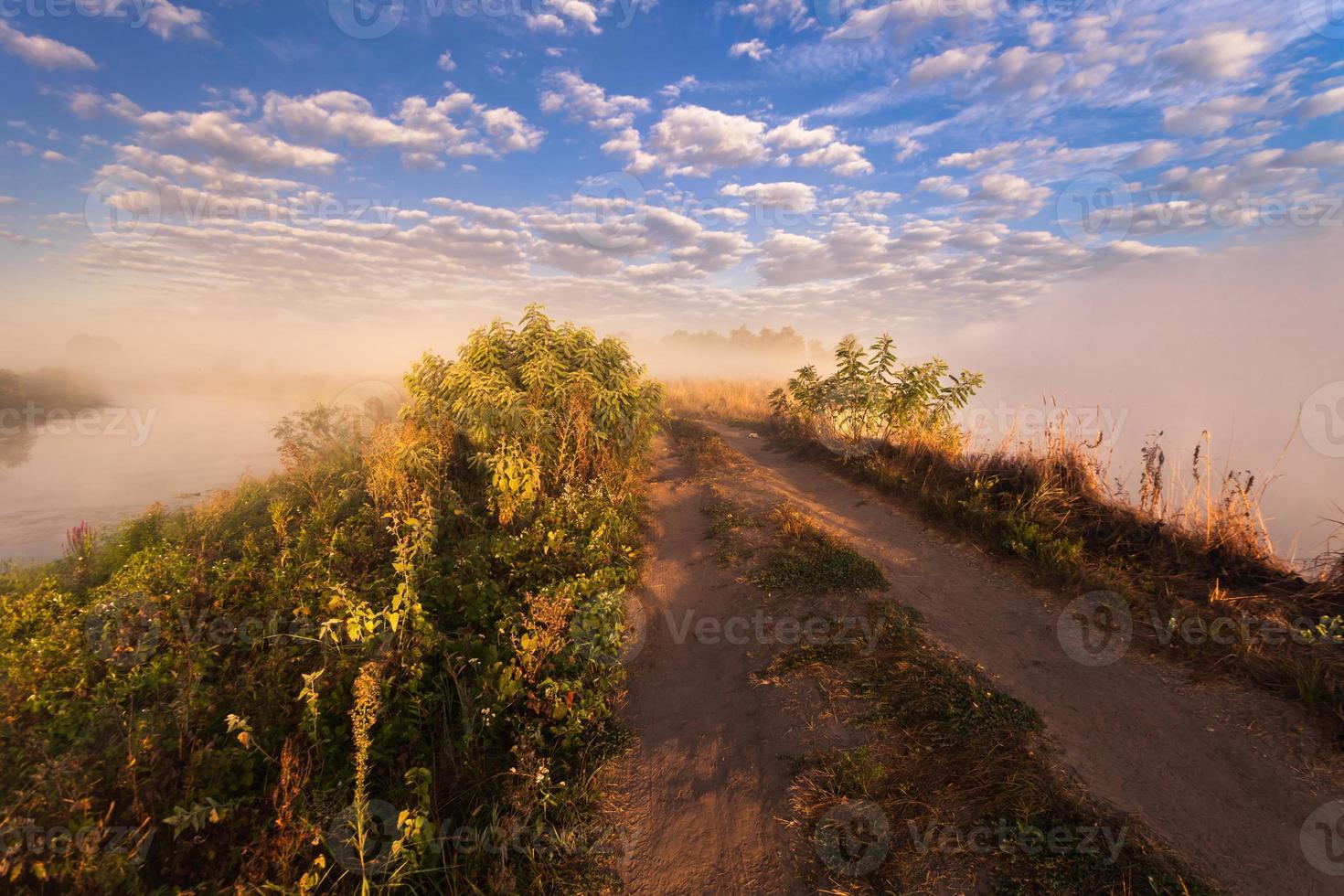 nebliger Morgen am Fluss und Wolken im Wasser foto