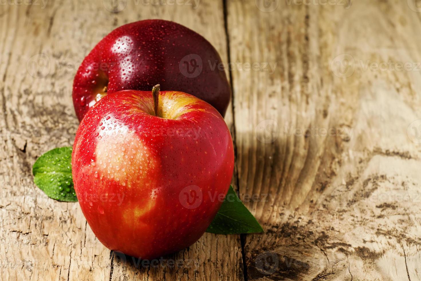 zwei rote Äpfel mit Wassertropfen auf einem Holztisch foto