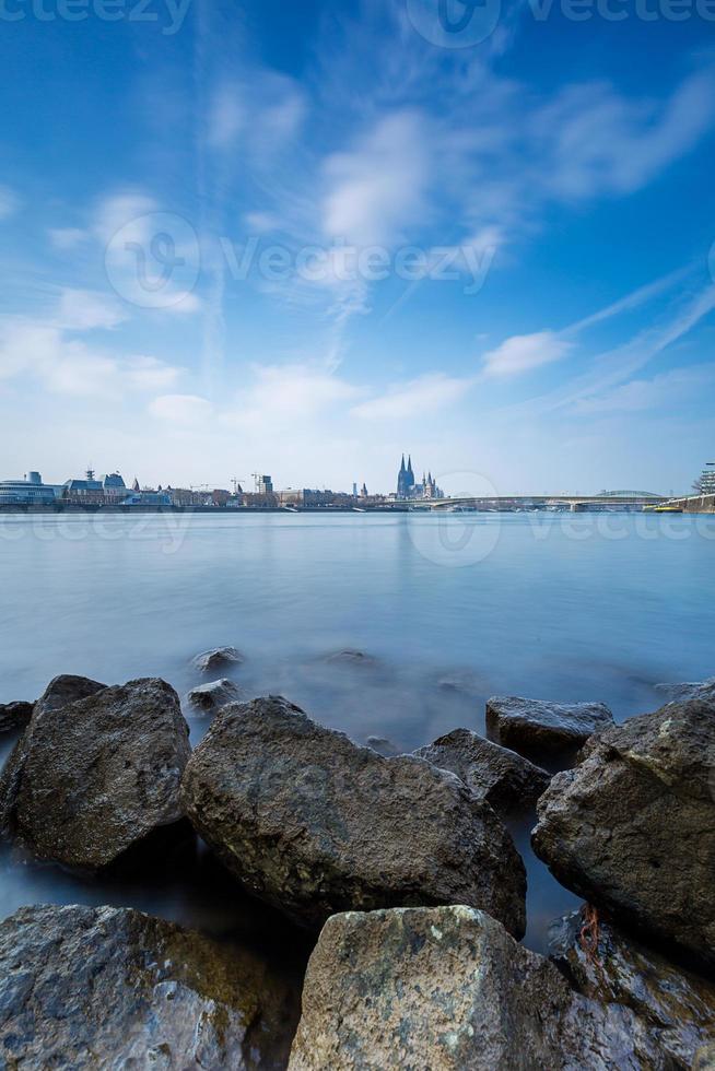 Kölner Cityskyline mit Dom am steinigen Rheinufer foto