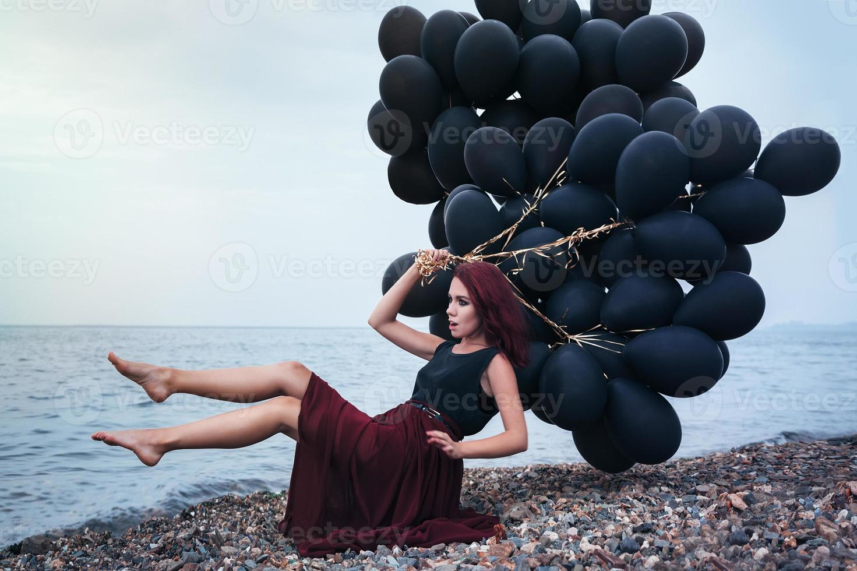 schönes Mädchen, das mit schwarzen Luftballons geht foto