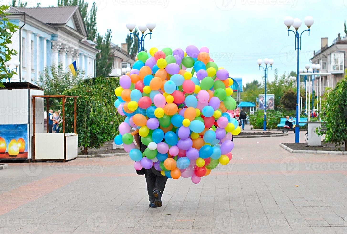 Mann trägt viele helle Luftballons foto