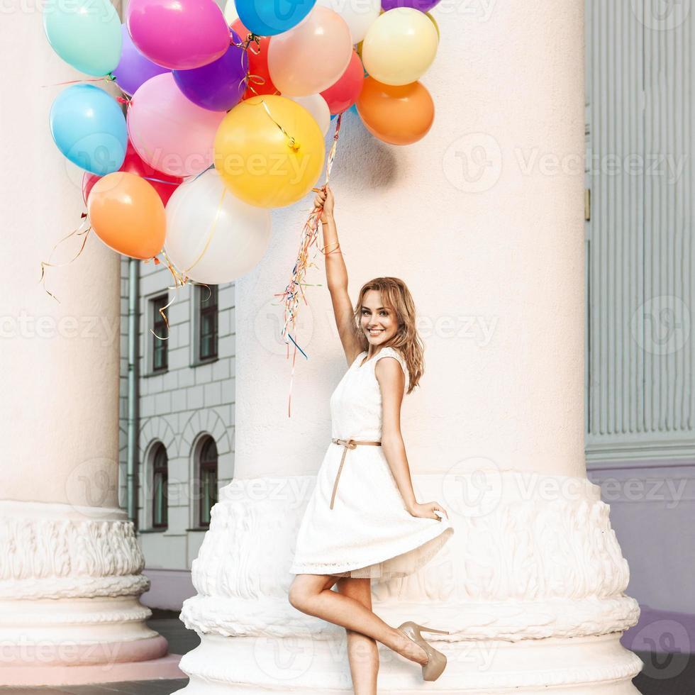schöne Dame, die ein Bündel Luftballons hält foto