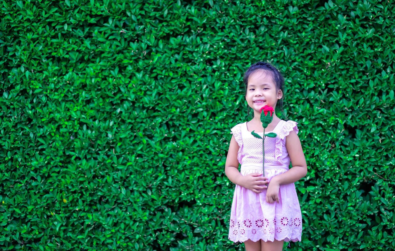 niedliches kleines Mädchen im Kleid, das eine rote Rose im Park hält foto