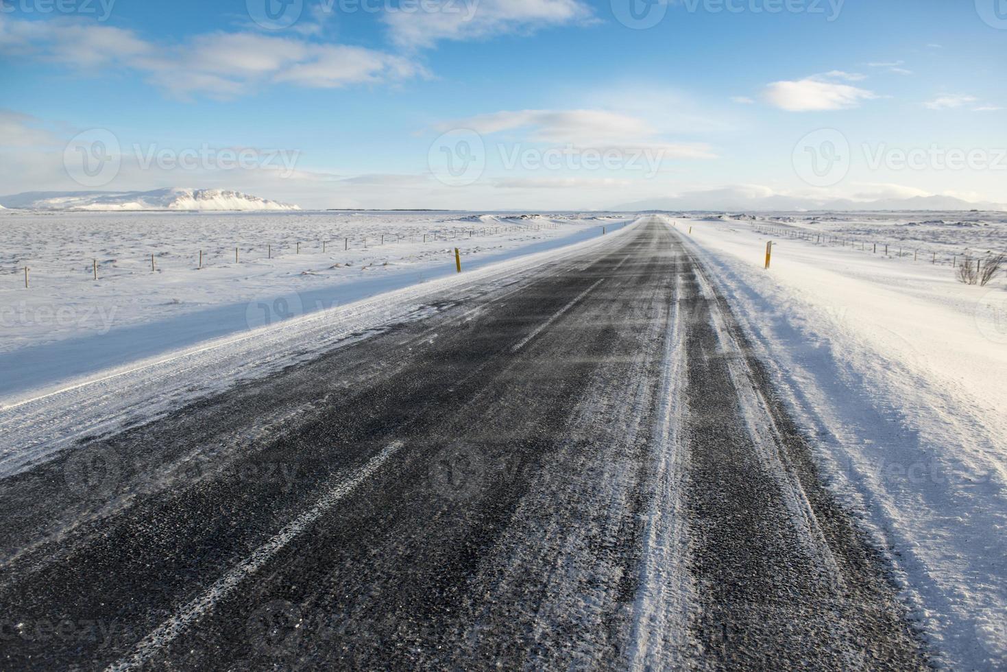 Winterasphaltstraße bedeckt durch Schnee, Island foto