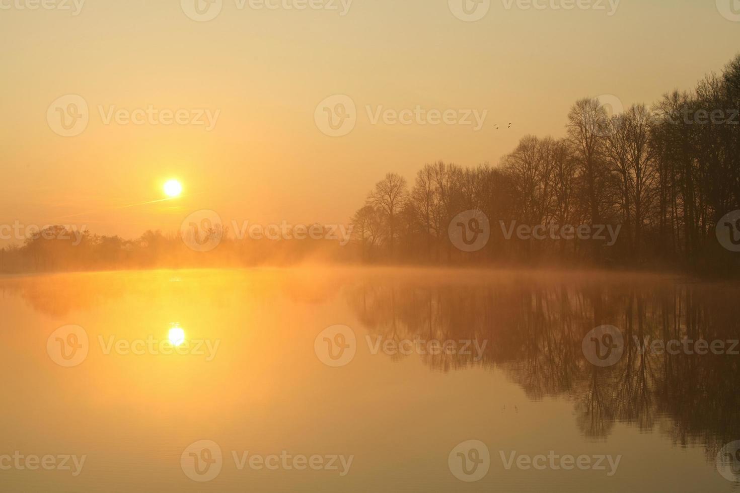 Sonnenaufgang auf einem nebligen See foto