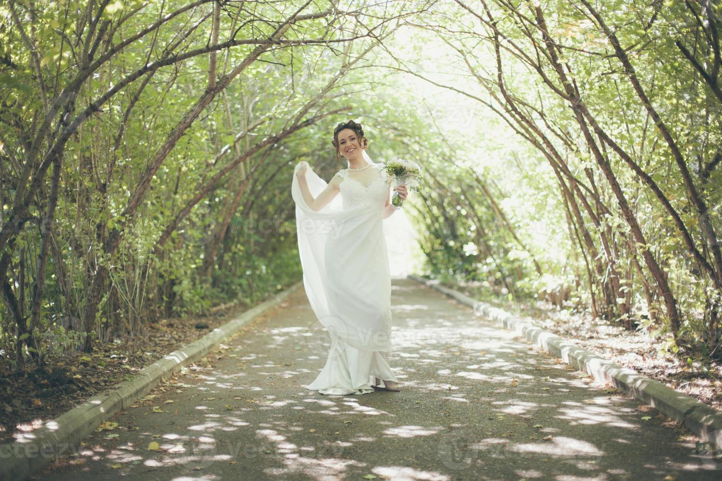 Braut, die Hochzeitskleid allein trägt foto